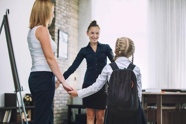 Piękne dzieci w wieku szkolnym, nauczycielka i matka rodziców razem w klasie w szkole otrzymują edukację szczęśliwą