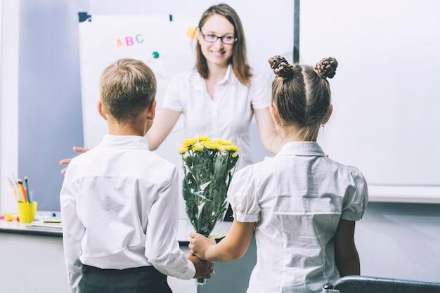 Piękne dzieci w wieku szkolnym z kwiatami dla nauczycieli w szkole na wakacjach