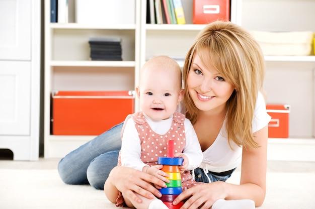 Piękne dziecko bawi się zabawkami z szczęśliwą matką w pomieszczeniu