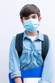 Piękne dziecko chłopiec uczeń z plecakiem i maską trzymając książki na białym tle
