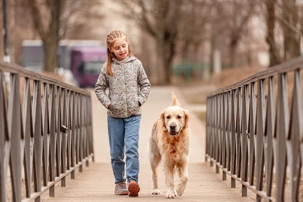 Piękne dziecko dziewczynka spaceru z psem golden retriever na moście w okresie wiosennym
