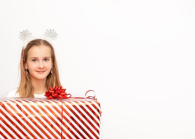 Piękne dziecko dziewczynka trzyma pudełko świąteczne czerwone paski ze wstążką i kokardą w dłoniach. na głowie są płatki śniegu.