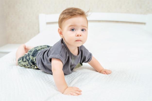 Piękne dziecko leżące na brzuchu w łóżku rodziców. śliczny dzieciak czołgał się na łóżku w białej słonecznej sypialni.