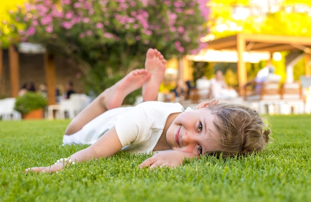 Piękne dziecko pozuje na trawie w parku