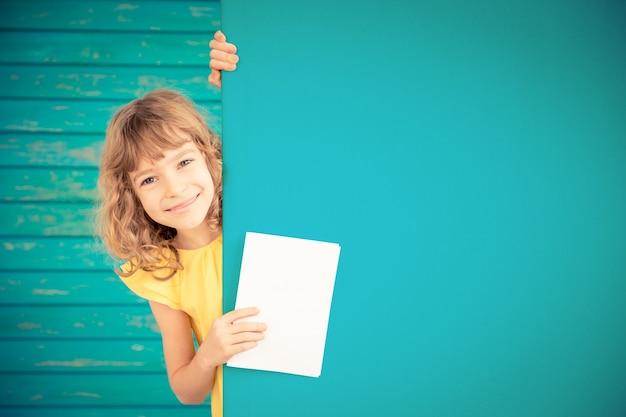 Piękne dziecko z kartą podarunkową za banerem puste wiosenne rodzinne wakacje koncepcja dzień ojca