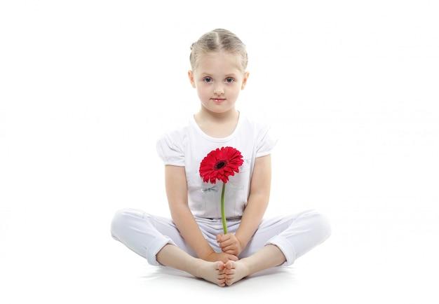 Piękne dziecko z kwiatem gerbera pozowanie na białym tle