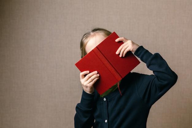 Piękne dziecko zasłaniające twarz książką.