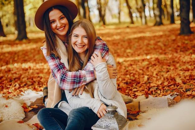 Piękne dziewczyny bawią się w jesiennym parku