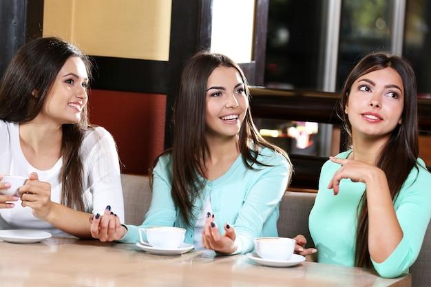 Piękne dziewczyny bawią się w kawiarni