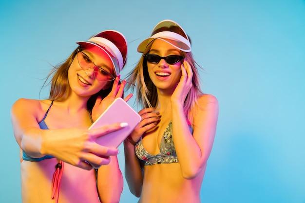 Piękne dziewczyny na białym tle na niebieskiej ścianie w świetle neonu