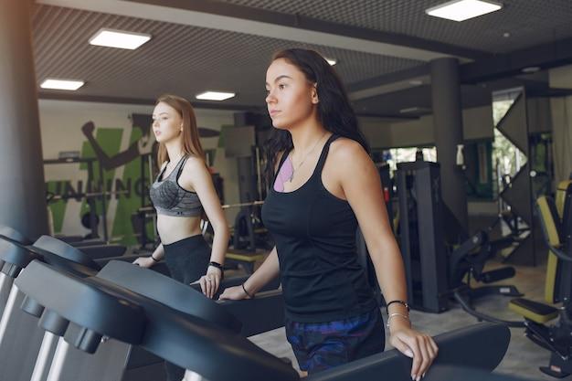 Piękne dziewczyny na siłowni. sportowe panie w odzieży sportowej. przyjaciele na torze wyścigowym.