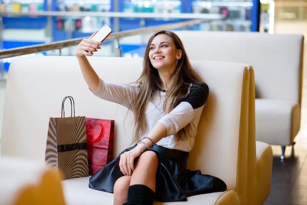 Piękne dziewczyny robią selfi w centrum handlowym.