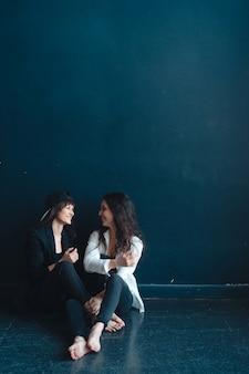Piękne dziewczyny siedzą przy ścianie i pozują