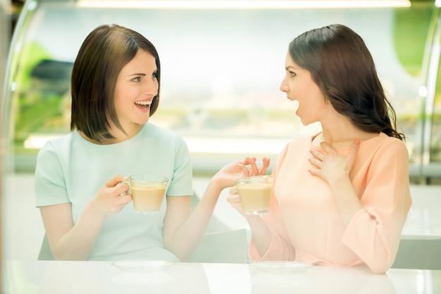 Piękne dziewczyny siedzą w miejskiej kawiarni i dzielą się sekretami.