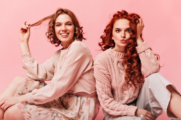 Piękne dziewczyny siedzące na różowym tle i dotykające kręconych włosów. widok z przodu przyjaciół pozujących na podłodze.