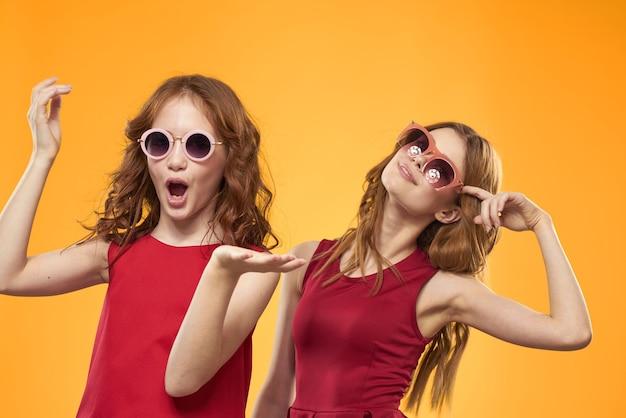 Piękne dziewczyny w identycznych ubraniach z okularami przeciwsłonecznymi