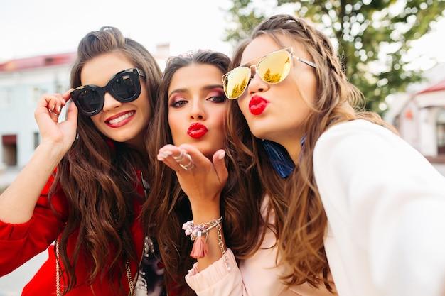 Piękne dziewczyny w okularach przeciwsłonecznych pokazuje znaki pokoju