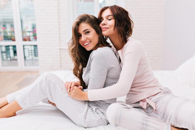 Piękne dziewczyny w piżamie na łóżku. dziewczyna z kręconymi włosami przytula od tyłu inną dziewczynę i trzyma oczy zamknięte.