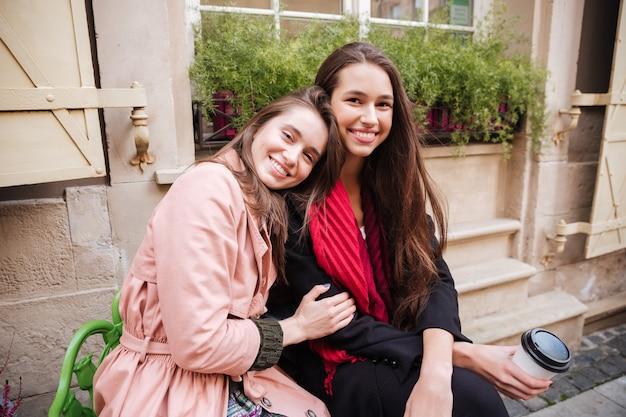 Piękne dziewczyny w płaszczach siedzą na ulicy.