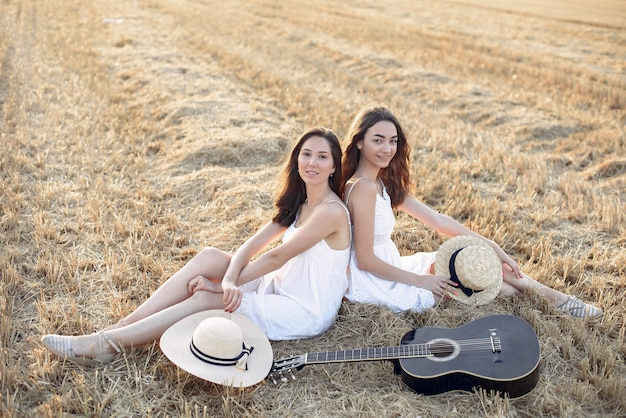 Piękne eleganckie dziewczyny w polu pszenicy jesienią