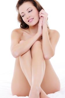 Piękne eleganckie kobiety nago siedzi na łóżku z rękami na twarzy