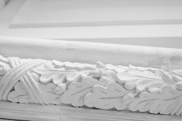 Piękne elementy luksusowego projektu ściany, białe listwy sztukatorskie na jasnym tle, antyczne tynkowanie