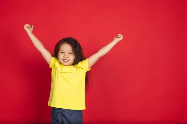Piękne emocjonalne dziewczynki na białym tle na czerwonej przestrzeni. półdługi portret szczęśliwego dziecka pokazujący gest i skierowany ku górze. pojęcie wyrazu twarzy, ludzkie emocje, dzieciństwo.