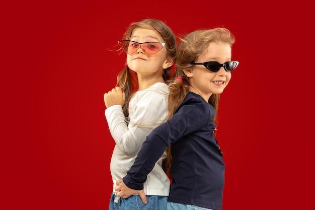 Piękne emocjonalne dziewczynki na białym tle na czerwonej przestrzeni
