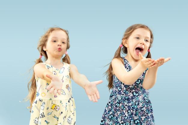 Piękne emocjonalne dziewczynki na białym tle. portret szczęśliwych sióstr lub przyjaciół ubranych w sukienki i grających. pojęcie wyrazu twarzy, ludzkie emocje, dzieciństwo.