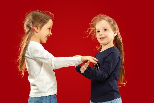 Piękne emocjonalne dziewczynki na czerwono