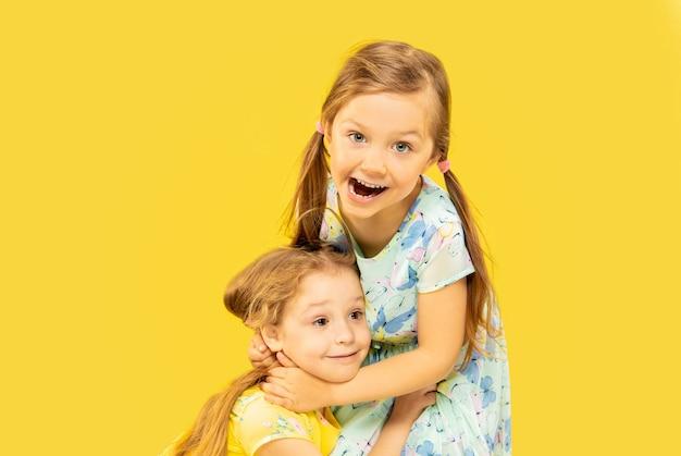 Piękne emocjonalne dziewczynki na żółtym tle