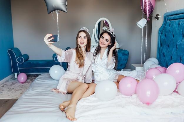 Piękne fantazyjne panie trzymają napój z balonami
