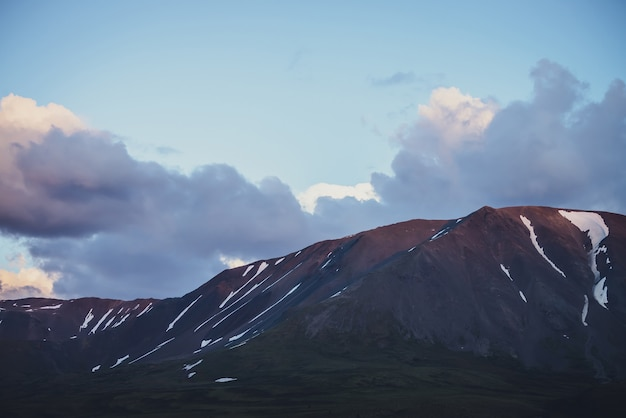 Piękne fioletowe góry skaliste ze śniegiem pod pochmurnym niebem zmierzchu. atmosferyczny zachód górskiej scenerii. niesamowite skały pod fioletowymi chmurami na niebie błękitnego wschodu słońca. niebo zmierzchu. wieczór górski krajobraz.