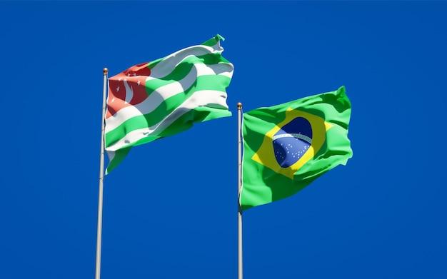 Piękne flagi państwowe brazylii i abchazji razem na błękitnym niebie