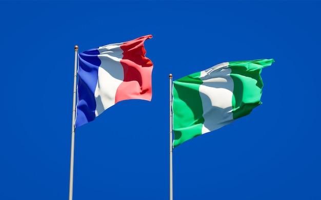 Piękne flagi państwowe francji i nigerii razem na błękitnym niebie