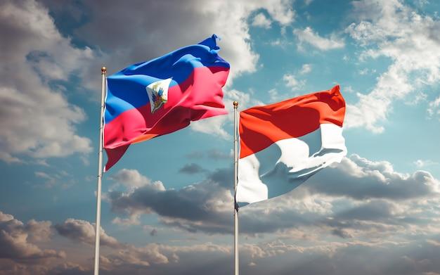 Piękne flagi państwowe haiti i indonezji razem na błękitnym niebie