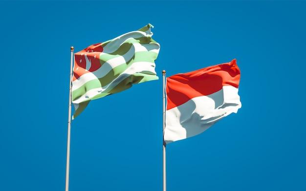 Piękne flagi państwowe indonezji i abchazji razem na błękitnym niebie