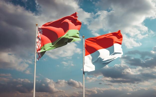 Piękne flagi państwowe indonezji i białorusi razem na błękitnym niebie