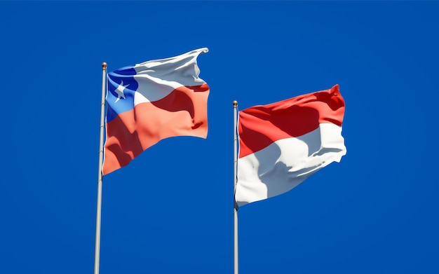 Piękne flagi państwowe indonezji i chile razem na błękitnym niebie