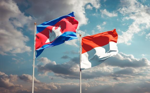 Piękne flagi państwowe indonezji i kambodży razem na błękitnym niebie