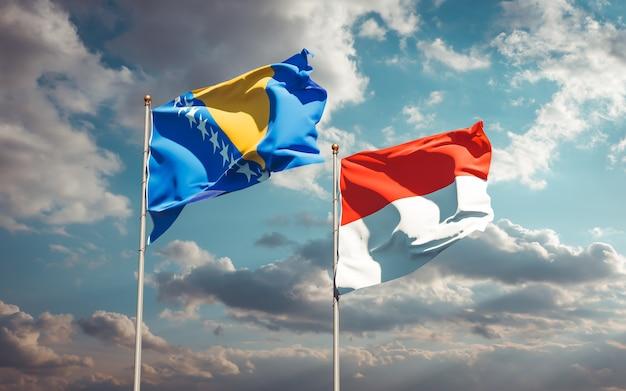 Piękne flagi państwowe indonezji oraz bośni i hercegowiny razem na błękitnym niebie