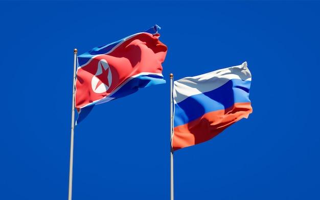 Piękne flagi państwowe korei północnej i rosji razem na błękitnym niebie. grafika 3d