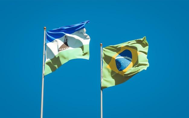 Piękne flagi państwowe lesotho i brazylii razem na błękitne niebo