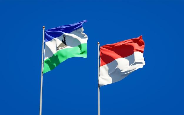 Piękne flagi państwowe lesotho i indonezji razem na błękitnym niebie