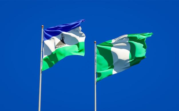 Piękne flagi państwowe lesotho i nigerii razem na błękitnym niebie