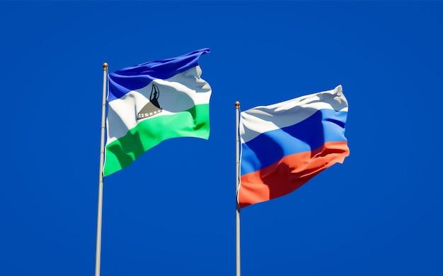 Piękne flagi państwowe lesotho i rosji razem na błękitnym niebie. grafika 3d