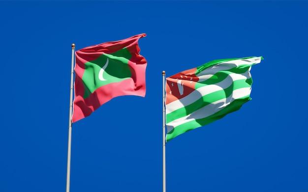 Piękne flagi państwowe malediwów i abchazji razem na błękitnym niebie. grafika 3d