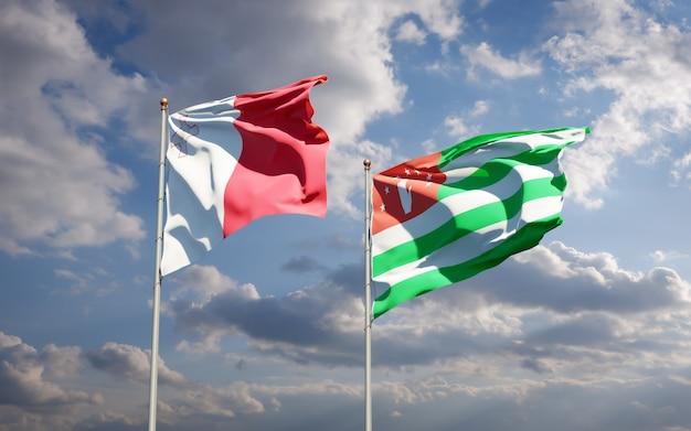 Piękne flagi państwowe malty i abchazji razem na błękitnym niebie. grafika 3d