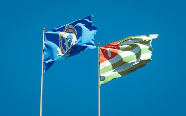 Piękne flagi państwowe mariany północne i abchazji razem na błękitne niebo. grafika 3d