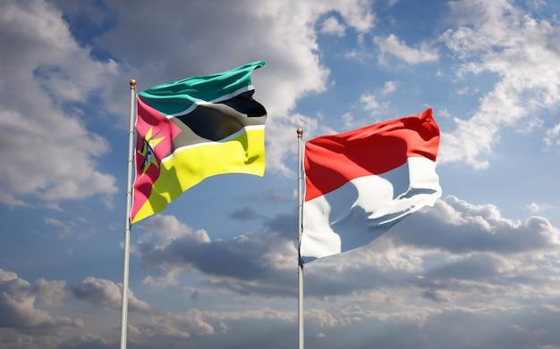 Piękne flagi państwowe mozambiku i indonezji razem na błękitnym niebie
